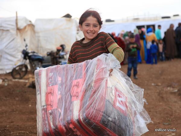 7人の兄妹のために毛布を嬉しそうに運ぶシリア難民の女の子
