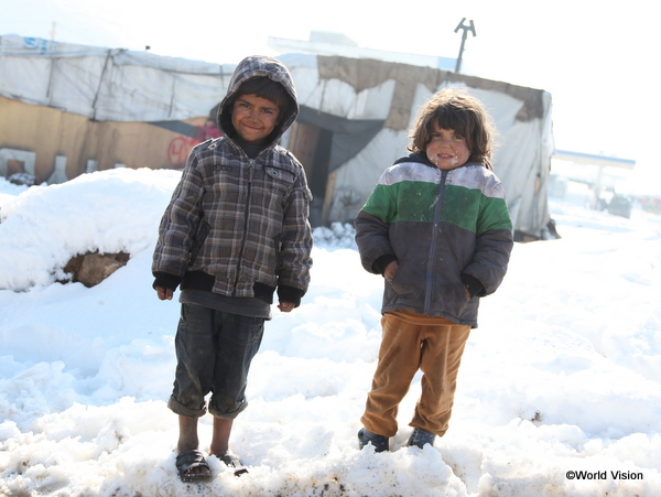 両親がいない兄妹。1 つしかないブーツを妹(右)に履かせてあげるため、サンダルで雪の中を歩くシリア難民のお兄ちゃん(左)