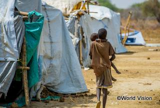 南スーダン国内の避難民キャンプで、幼い妹を抱いて歩く少年