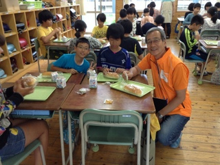 補食支援による給食を食べる益城町の子どもたちとWVJ事務局長 片山