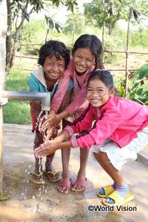 チャイルド・スポンサーシップの支援でできた井戸で手を洗う子どもたち(カンボジア)