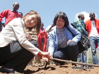 ソーラーポンプシステムでくみあげた水を活用する灌漑用の水道管を手に。福田氏(右)木内(左)