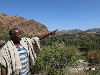丘が緑化されたことで洪水が減り、果物の収穫量が3倍になったと語る男性(写真:ケニア)