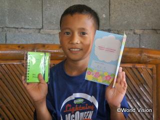 日本のチャイルド・スポンサーからのグリーティングカードとプレゼントを受け取り笑顔のジョン君