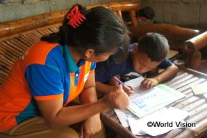 返事を書くジョン君とワールド・ビジョンの地域ボランティアをしているお母さん