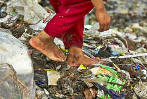 危険なゴミ山を踏みしめている裸足の足