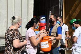 被災した家族に衛生キットを配布するWVスタッフ