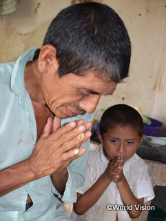 平和を願って祈る父と子