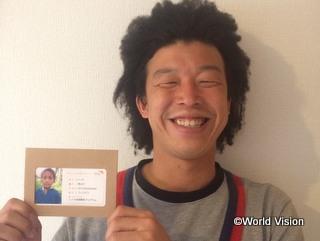 チャイルドの写真を持っている横田さん