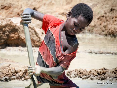 採掘場で泥まみれになりながらわずかな金を探すヨハネ君(モザンビーク)