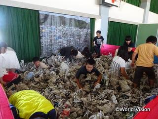 ゴミ山で売れるものを探す児童労働を疑似体験する小学生