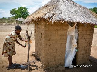 支援によって建てられたトイレの前で手洗いをする女の子