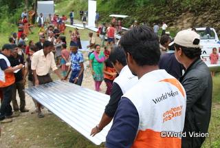 屋根用鋼板をコミュニティの人々と運ぶスタッフ