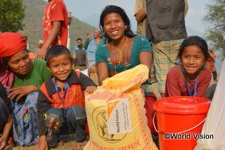 支援物資を受け取り、笑顔を浮かべる家族
