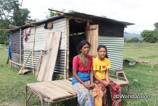 ギネンドラさん(右)とお母さん。後ろに見えるのは、支援物資で建てた仮設住居