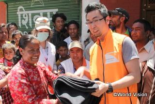 日本からは、坂賢二郎(ばん・けんじろう)スタッフが現地で事業調整にあたりました。写真は、カトマンズ郊外で被災者に毛布を届ける坂スタッフ