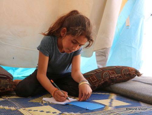 紛争により避難したテントで勉強するシリアの子ども