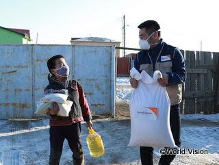 支援物資の食糧を男の子の家に届けるWVスタッフ(モンゴル)