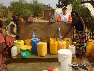 ワールド・ビジョンが建設したコミュニティ内の給水所で水をくむ女性