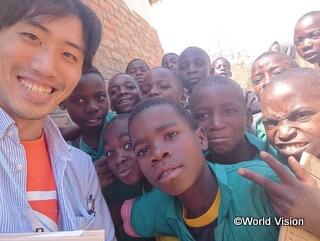 マラウイの支援地の小学生たちと李スタッフ